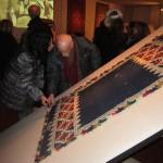 Italo Picini osserva un tessuto antico presente in Mostra